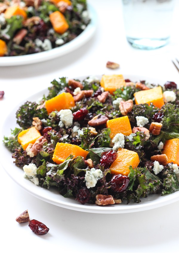 Holiday Kale Salad- tossed in an apple cider mustard vinaigrette and topped with roasted butternut squash, cranberries, and candied maple pecans!