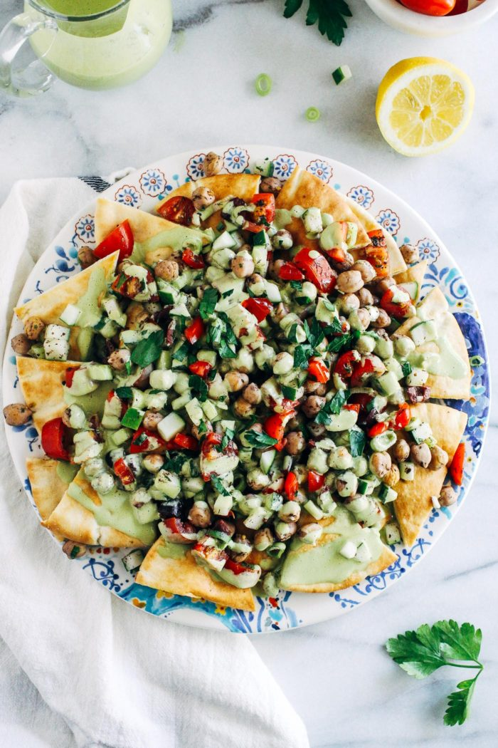 Fresh Greek Nachos with Herbed Tahini Sauce- toasted pita wedges topped with marinated Greek chickpea salad and a tangy herbed tahini sauce. No one will miss the cheese in these flavorful plant-based nachos!