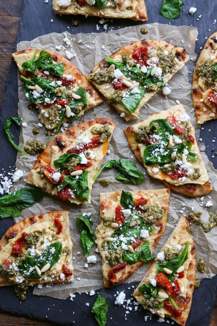 Hummus Flatbread with Sun-Dried Tomatoes, Spinach, and Pesto from The Roasted Root