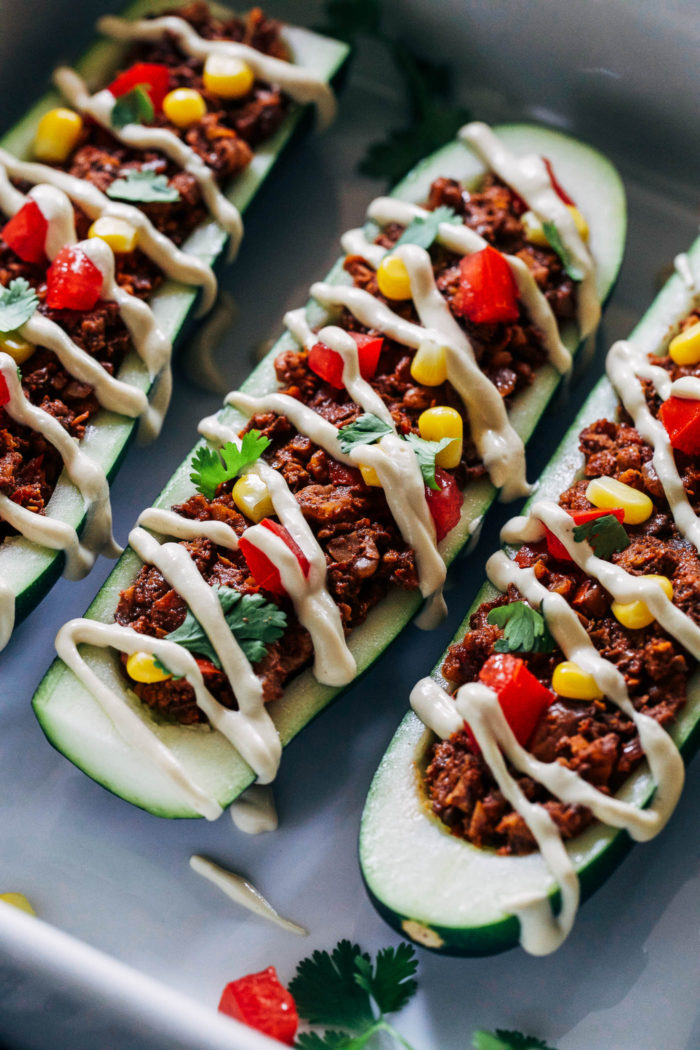Vegan Zucchini Taco Boats- chopped walnuts and mushrooms give these plant-based taco boats a hearty texture packed full of protein and healthy fats. Drizzled with a cheesy cashew cream for ultimate bliss. (vegan, grain-free and gluten-free)