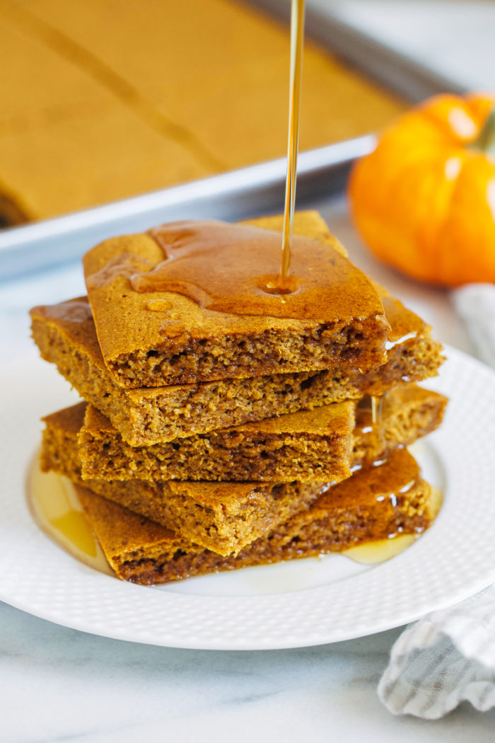 Pumpkin Sheet Pan Pancakes- forget standing over the skillet waiting for your pancakes to cook! These pancakes are baked, requiring less hands on time. Perfect for prep ahead breakfasts or serving guests!